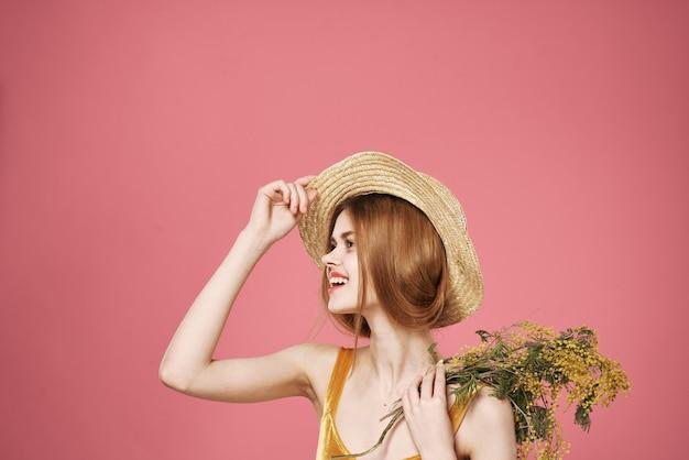 Ładna kobieta w kapeluszu bukiet kwiatów prezent na wakacje różowe tło