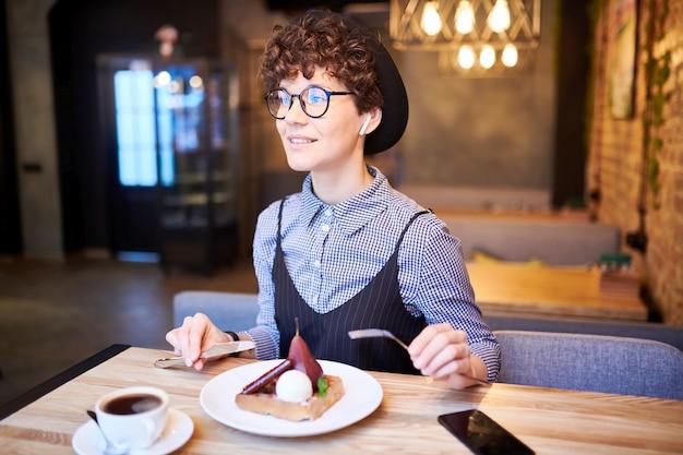 Ładna kobieta w kapeluszu i elegancki dorywczo siedzi przy stole w kawiarni, relaksując się i delektując się smacznym deserem
