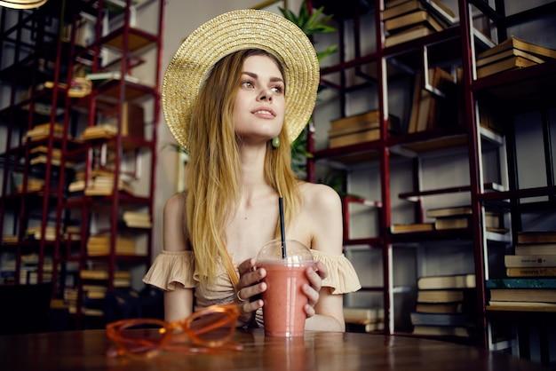 Ładna kobieta w kapeluszu, picie soku w kawiarni wakacje styl życia. wysokiej jakości zdjęcie