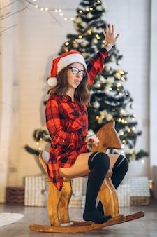Ładna kobieta w koszuli i skarpetkach dobrze się bawi, jeżdżąc na drewnianej huśtawce z koniem