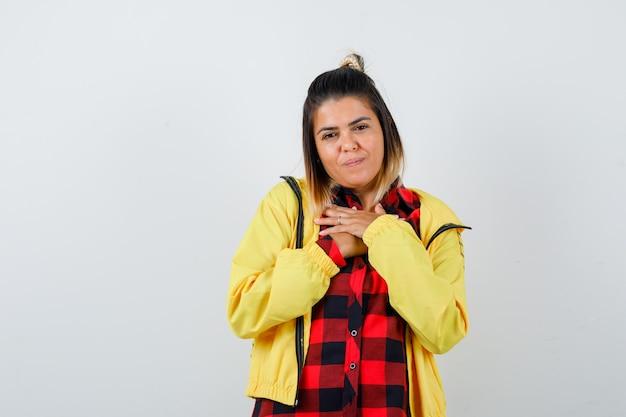 Ładna kobieta w koszuli, kurtce, trzymając się za ręce na klatce piersiowej i patrząc wdzięczny, widok z przodu.
