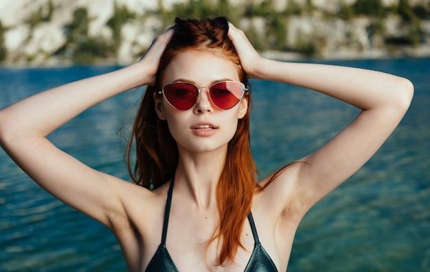 Ładna kobieta w krajobrazie luksusowych okularów przeciwsłonecznych zielony strój kąpielowy