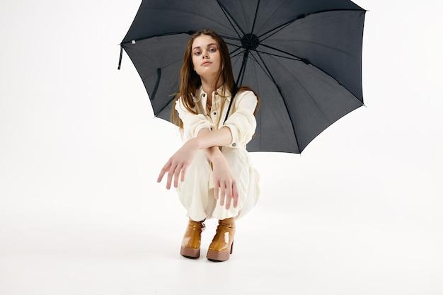 Ładna kobieta w kucki otwarty parasol moda nowoczesny styl.