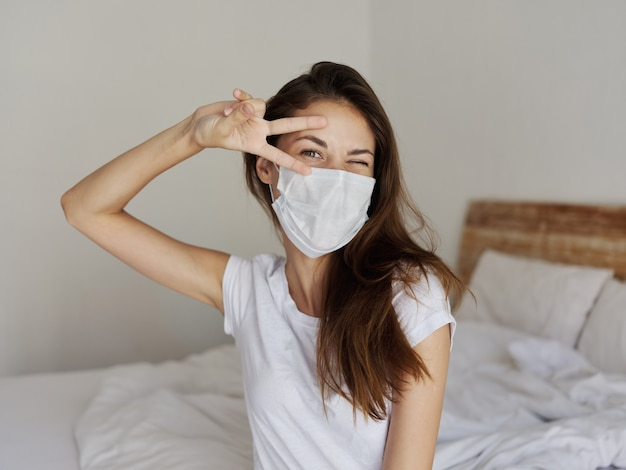 Ładna kobieta w masce medycznej trzyma dwa palce w pobliżu twarzy i siada na łóżku