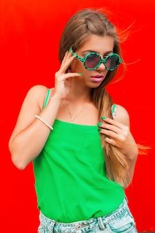 Ładna kobieta w modnych okrągłych okularach przeciwsłonecznych w pobliżu czerwonej ściany