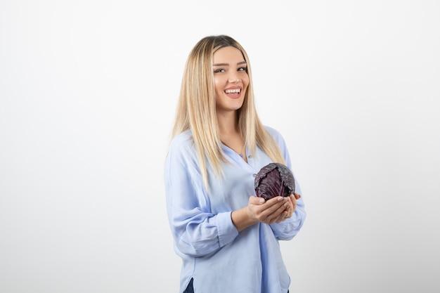 Ładna kobieta w niebieskim stroju trzymając jedną kapustę na białej ścianie.