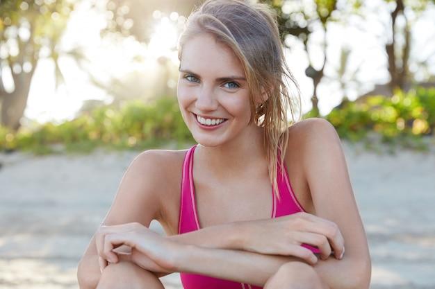 Ładna kobieta w odzieży sportowej na plaży