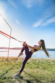 Ładna kobieta w odzieży sportowej robi pompki crossfit z paskami fitness trx na świeżym powietrzu w pobliżu jeziora w ciągu dnia. zdrowy tryb życia
