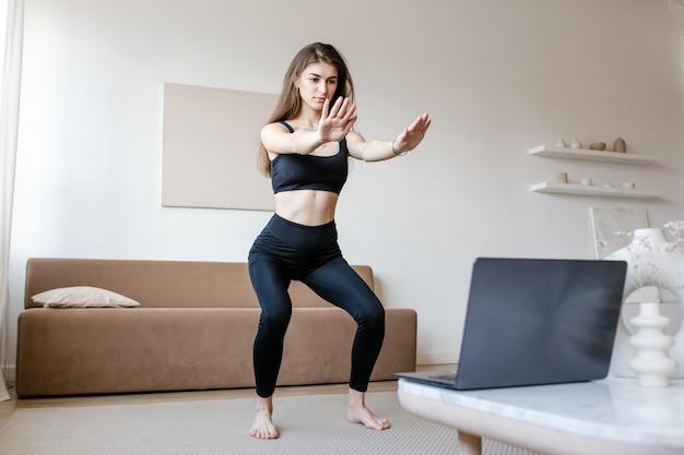Ładna kobieta w odzieży sportowej wykonuje ćwiczenia jogi, prowadzi zdrowy tryb życia i korzysta z laptopa