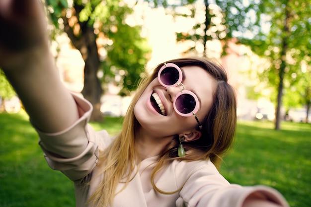 Ładna kobieta w okularach przeciwsłonecznych w letnim stylu życia w parku