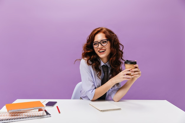 Ładna kobieta w okularach trzyma filiżankę kawy