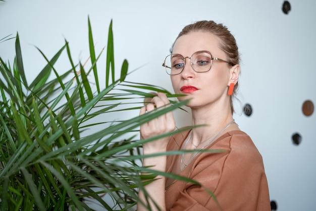 Ładna kobieta w okularach w pobliżu zielonego kwiatu w pomieszczeniu patrzy na długie liście