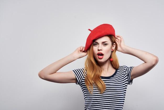 Ładna kobieta w pasiastym tshirt czerwonych ustach gest z rękami na białym tle