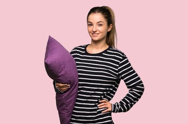 Ładna kobieta w piżamie pozuje z rękami przy biodrem i ono uśmiecha się na odosobnionej menchii ścianie