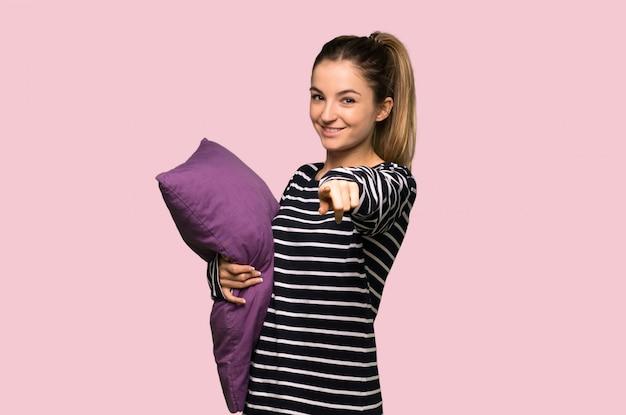 Ładna kobieta w piżamie wskazuje palcem na ciebie z pewnym siebie wyrazem na odosobnionej różowej ścianie