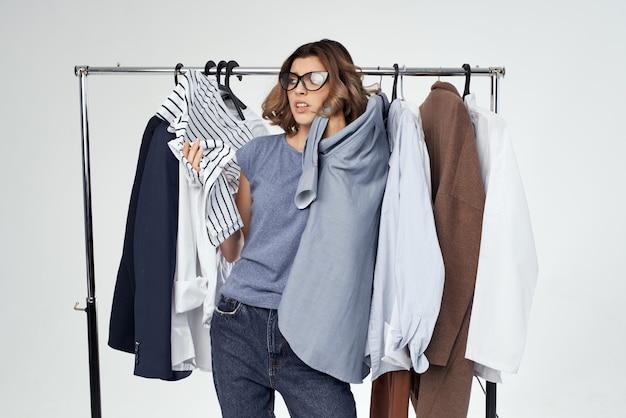 Ładna kobieta w pobliżu ubrania zakupoholiczka na białym tle. zdjęcie wysokiej jakości