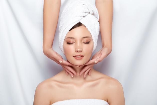 Ładna kobieta w ręczniku dostaje masaż szyi i twarzy