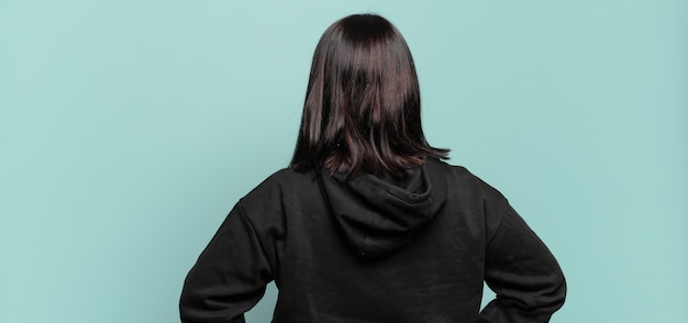 Ładna kobieta w rozmiarze plus size czuje się zagubiona lub pełna, ma wątpliwości i pytania, zastanawia się, z rękami opartymi na biodrach, widok z tyłu