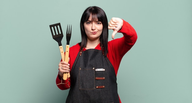 Ładna kobieta w rozmiarze plus size czuje się zła, zła, zirytowana, rozczarowana lub niezadowolona, pokazuje kciuki w dół z poważnym spojrzeniem