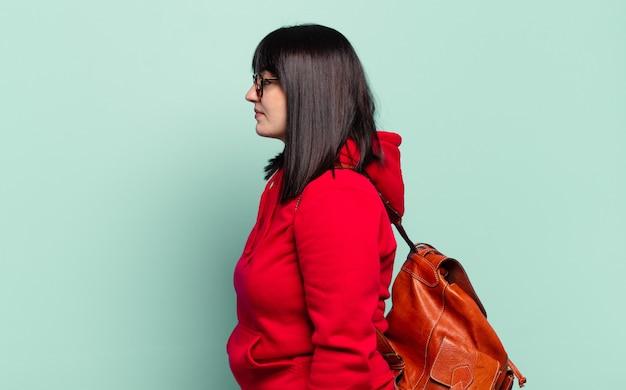 Ładna kobieta w rozmiarze plus size w widoku profilu, która chce skopiować przestrzeń przed siebie, myśleć, wyobrażać sobie lub marzyć