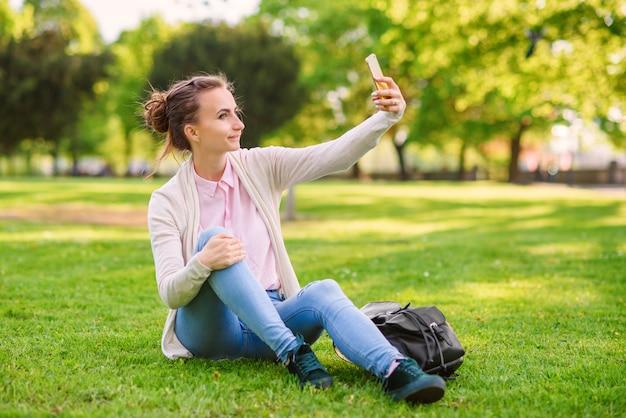Ładna kobieta w różowej bluzce i niebieskim drelichu siedzi na trawie i robi selfie