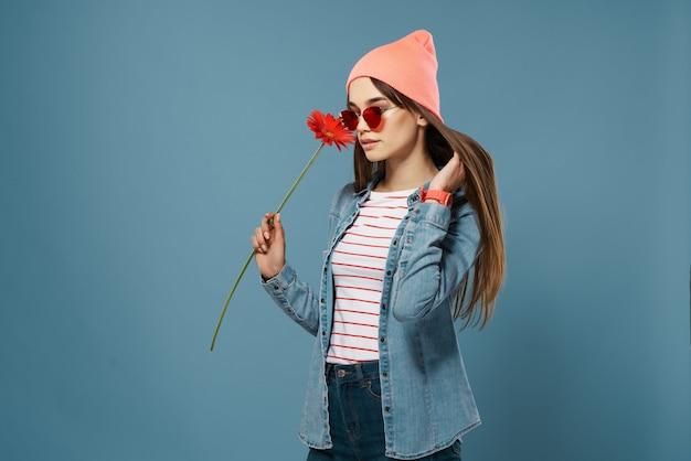 Ładna kobieta w różowym kapeluszu czerwony kwiat róża romans niebieskim tle. zdjęcie wysokiej jakości
