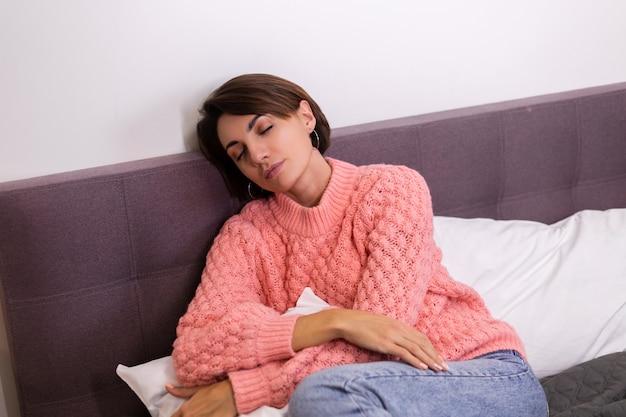 Ładna kobieta w różowym uroczym sweterku z dzianiny siedzi w domu w łóżku, uśmiechnięta, ciesząc się samotnością