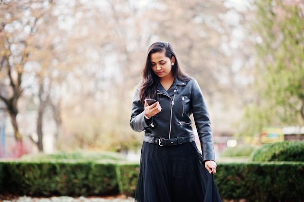 Ładna kobieta w sari sukience i skórzanej kurtce pozował na zewnątrz na jesiennej ulicy i patrząc na telefon komórkowy.