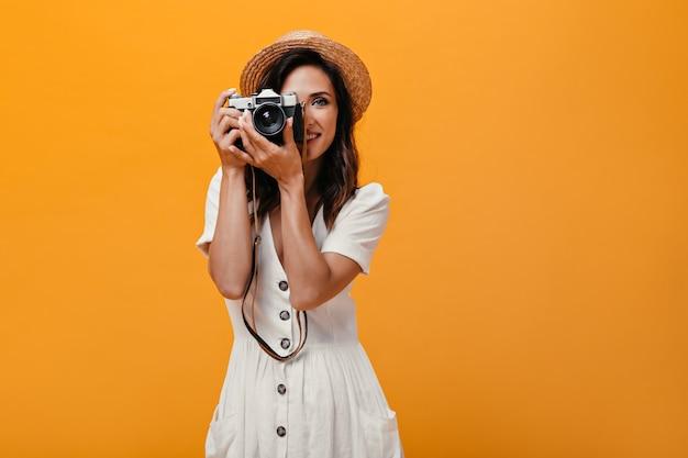 Ładna kobieta w słomkowym kapeluszu, trzymając aparat retro na na białym tle