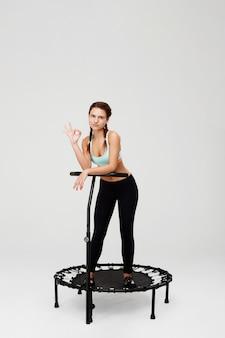 Ładna kobieta w sportowej odzieży pokazuje ok znaka patrzeje prosto