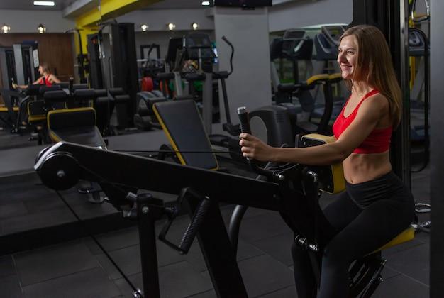 Ładna kobieta w sportwear ćwiczenia jedną ręką z maszyną wagi w nowoczesnej siłowni.