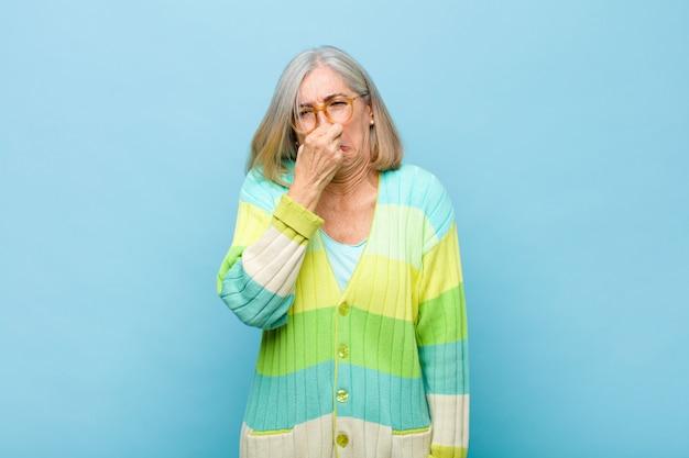 Ładna kobieta w średnim lub średnim wieku czująca się zniesmaczona, trzymająca nos, aby uniknąć zapachu obrzydliwego i nieprzyjemnego smrodu
