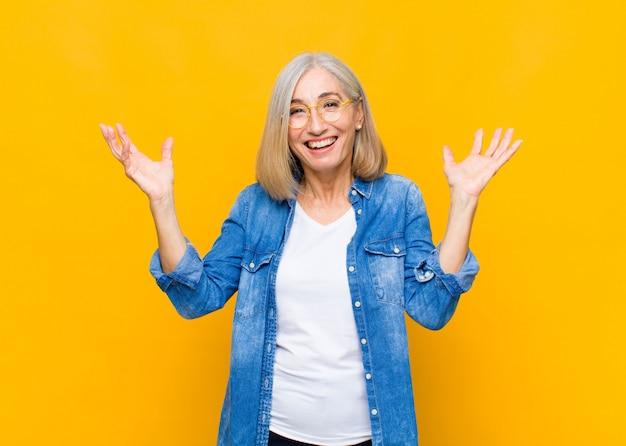 Ładna kobieta w średnim lub średnim wieku czuje się szczęśliwa, zdziwiona, szczęśliwa i zaskoczona, świętując zwycięstwo obiema rękami w powietrzu