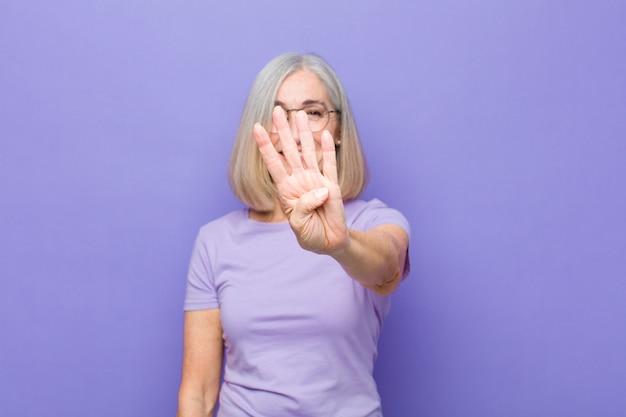 Ładna kobieta w średnim lub średnim wieku, uśmiechnięta i wyglądająca przyjaźnie, pokazująca numer cztery lub czwarty ręką do przodu, odliczająca w dół