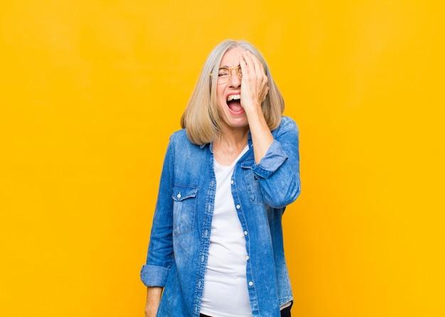 Ładna kobieta w średnim lub średnim wieku, wyglądająca na senną, znudzoną i ziewającą, z bólem głowy i dłonią pokrywającą połowę twarzy