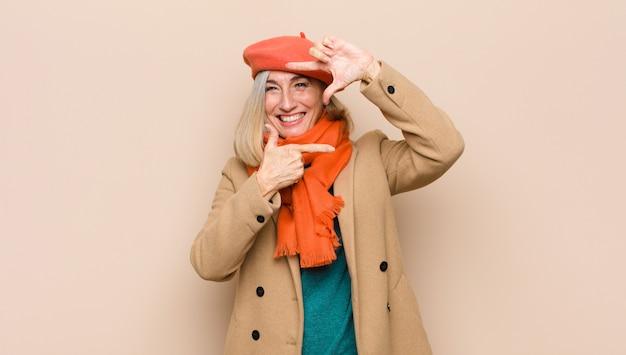 Ładna kobieta w średnim lub starszym wieku czuje się szczęśliwa, przyjazna i pozytywna, uśmiecha się i robi z rąk portret lub ramkę na zdjęcia