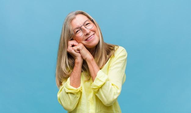 Ładna kobieta w średnim wieku czująca się szczęśliwa i zakochana, uśmiechnięta z jedną ręką przy sercu, a drugą wyciągniętą do przodu