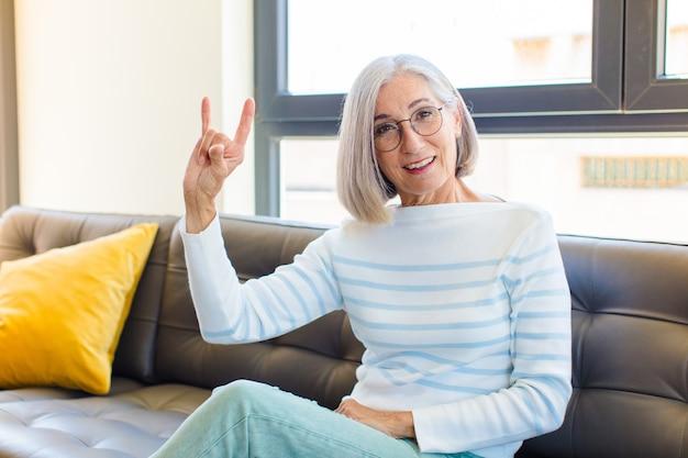Ładna kobieta w średnim wieku czująca się szczęśliwa, zabawna, pewna siebie, pozytywna i zbuntowana, robiąca ręką rockowy lub heavy metalowy znak