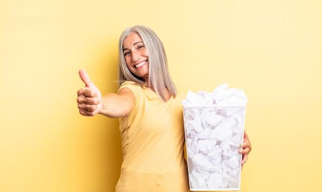 Ładna kobieta w średnim wieku czuje się dumna, uśmiecha się pozytywnie z kciukami do góry. koncepcja awarii kulek papierowych