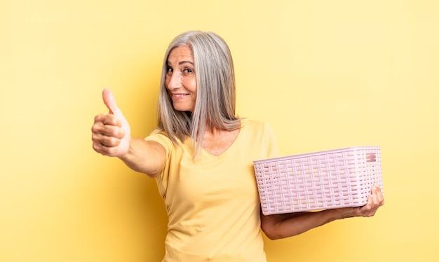 Ładna kobieta w średnim wieku czuje się dumna, uśmiecha się pozytywnie z kciukami do góry. koncepcja pustego koszyka
