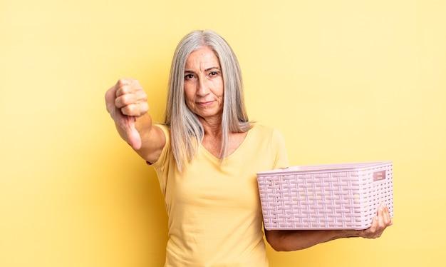 Ładna kobieta w średnim wieku czuje się krzyż, pokazując kciuk w dół. koncepcja pustego koszyka