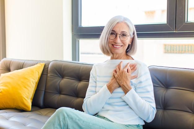 Ładna kobieta w średnim wieku czuje się romantycznie, szczęśliwa i zakochana, uśmiecha się radośnie i trzyma ręce blisko serca