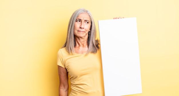 Ładna kobieta w średnim wieku czuje się smutna, zdenerwowana lub zła i patrzy w bok. koncepcja pustego płótna
