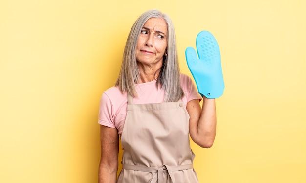 Ładna kobieta w średnim wieku czuje się smutna, zdenerwowana lub zła i patrzy w bok. koncepcja rękawic kuchennych