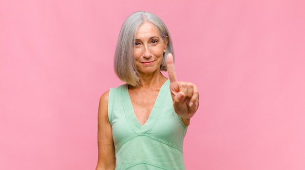 Ładna kobieta w średnim wieku czuje się szczęśliwa i odnosi sukcesy, uśmiecha się i klaszcze w dłonie, gratulując brawami
