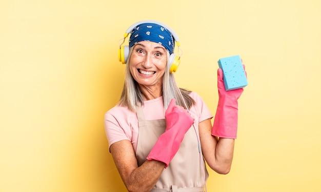 Ładna kobieta w średnim wieku czuje się szczęśliwa i staje przed wyzwaniem lub świętuje. czyścik do szorowania