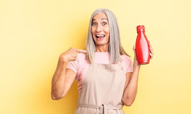 Ładna kobieta w średnim wieku czuje się szczęśliwa i wskazuje na siebie z podekscytowaniem. koncepcja ketchupu
