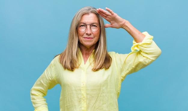 Ładna kobieta w średnim wieku czuje się zagubiona lub pełna, ma wątpliwości i pytania, zastanawia się, z rękami na biodrach, widok z tyłu