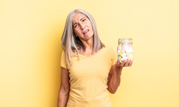Ładna kobieta w średnim wieku czuje się zakłopotana i zdezorientowana. koncepcja butelki cukierków
