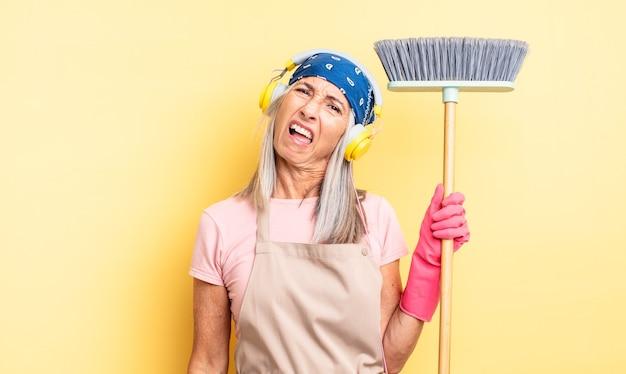 Ładna kobieta w średnim wieku czuje się zakłopotana i zdezorientowana. koncepcja gospodarstwa domowego i miotły